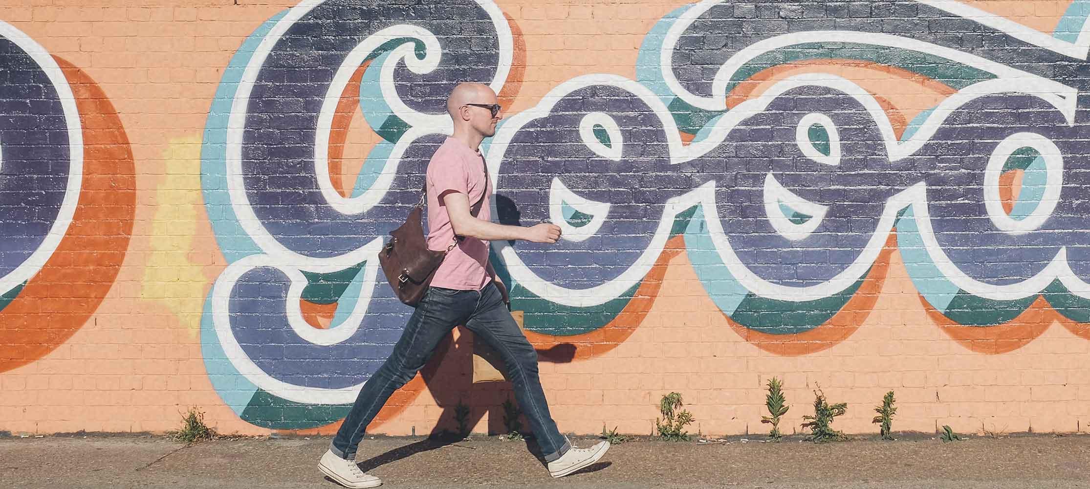 Mann läuft an Wand vorbei Follow-Me Gruppe